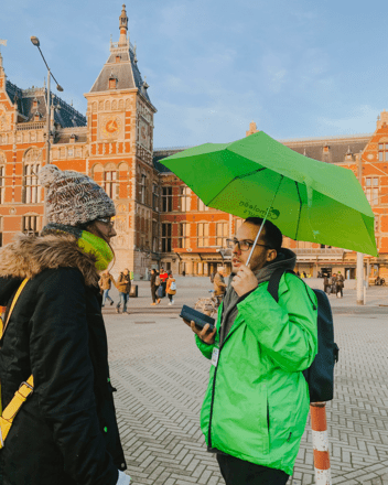 Free Walking Tour guide holding a green umbrella and talking to a traveler at the meeting point of the tour in Amsterdam.