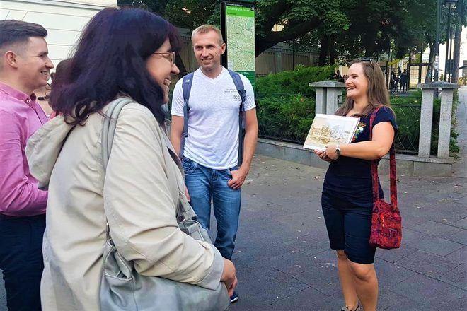 Guía de free tour enseña algo con sonrisa a su grupo de viajeros en Vilnius.