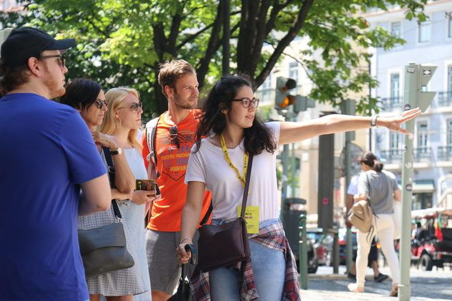 Tour guide showing something to travelers during a free walking tour in Lisbon with GuruWalk.