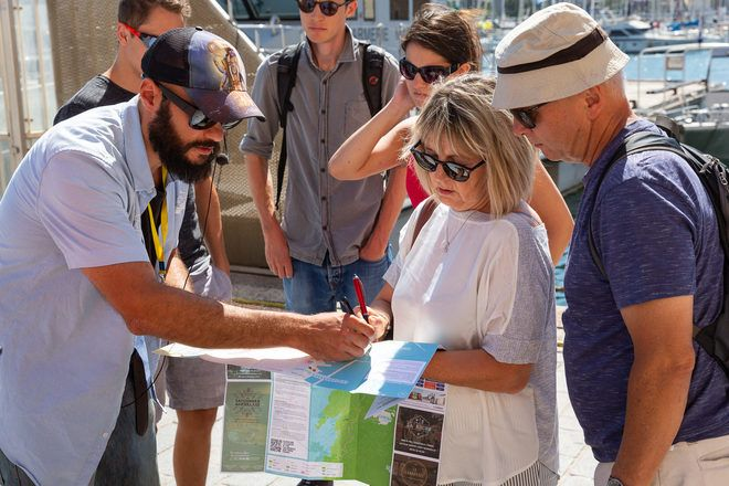 Tour leader shows on the map where to go after the tour in Marseille, France.