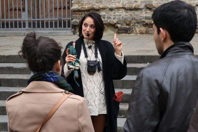Guía de GuruWalk hablando por un micrófono a sus viajeros en Florencia, Italia.