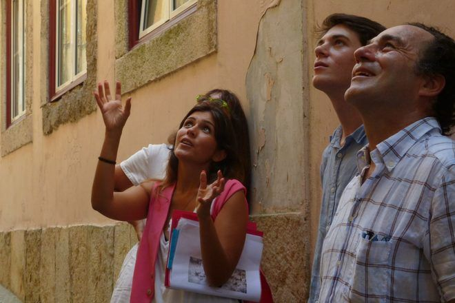 Tour guide showing something to a group of travelers in a street of Lisbon, Portugal, during a free walking tour with GuruWalk.