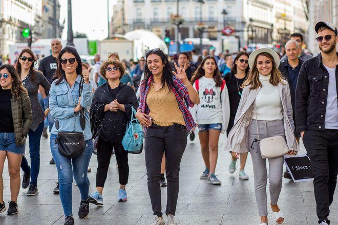 Guía de free tour de GuruWalk en Madrid camina en una calle con su grupo de viajeros.